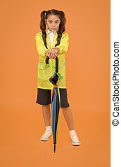 Cute schoolgirl feel protected for spring weather. Waterproof concept. Match your raincoat with umbrella. Schoolgirl wear raincoat. Small schoolgirl wear water resistant clothes for rainy day