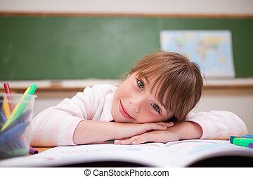 Cute schoolgirl leaning on a desk