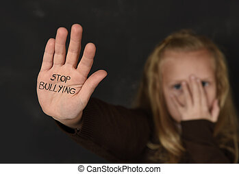 cute schoolgirl scared sad asking for help showing hands with stop bullying text written on her palm