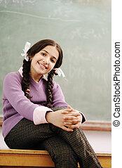 Cute schoolgirl siting on desk in classroom