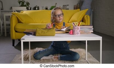 Cute schoolgirl studying with book at coffee table