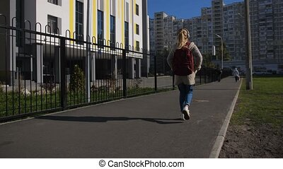 Cute schoolgirl with backpack going to school - Rear view of...
