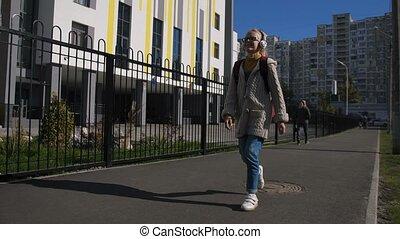 Cute schoolgirl with headphones walking to school