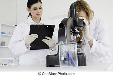 Cute scientist conducting an experiment with her assistant