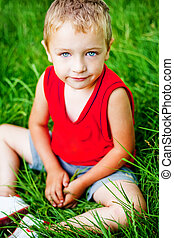 Cute serene kid on fresh green grass