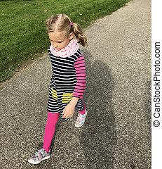 Cute seroius girl in pink scarf and leggings walking