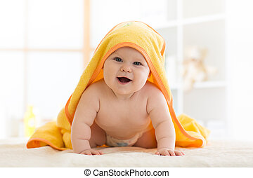 Cute seven months baby covered with yellow towel