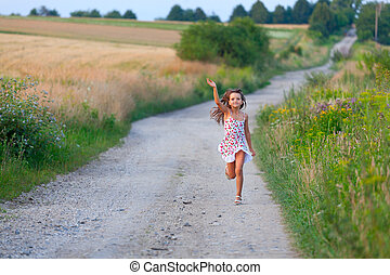 Cute seven years girl running in filds road on sunset summer day