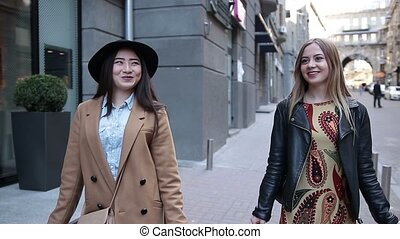 Cute shopping women walking with bags on street