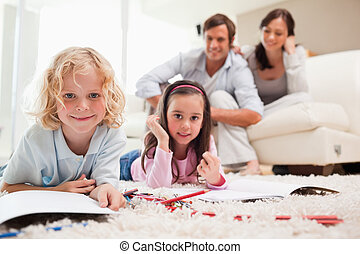 Cute siblings drawing while their parents are in the background