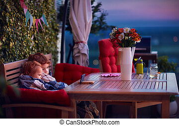 cute siblings having fun, watching cartoons on the phone, spending time on cozy rooftop patio on summer evening