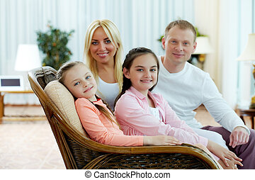 Cute siblings - Portrait of happy girls sitting on sofa with...