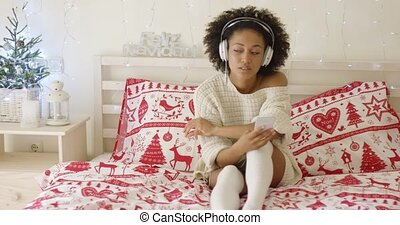 Cute single woman in long sweater on bed listening to music...