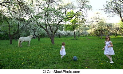 Cute sisters in white dress play with ball in blooming spring tree garden
