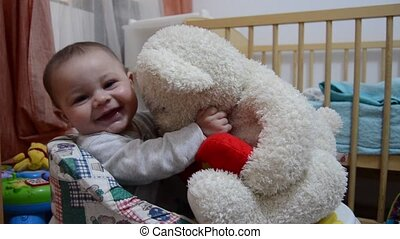 Cute six months old baby boy in the walker holding big white teddy bear, kissing him and pulling his ears