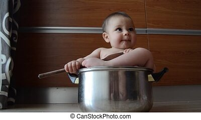 cute six months old baby boy playing with cooking pot and...