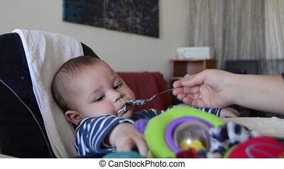 cute six months old baby boy trying to reach toy while mother is feeding him