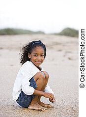 Cute six year old African-American girl playing on sand at beach