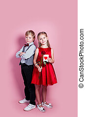 cute six year old girl with a Valentine's card in her hand and funny boy on pink background