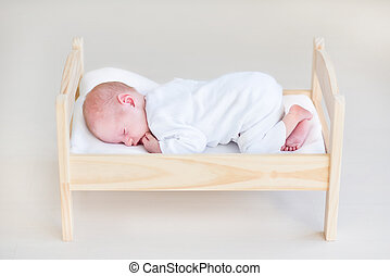 Cute sleeping newborn baby in a toy bed