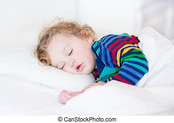 Cute sleeping toddler girl in a white bed