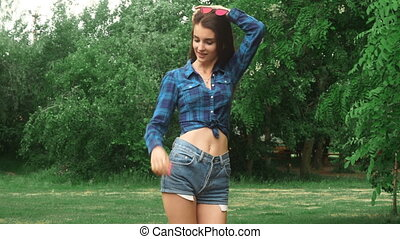 cute slim girl stands in the park and wind stirs her hair at...