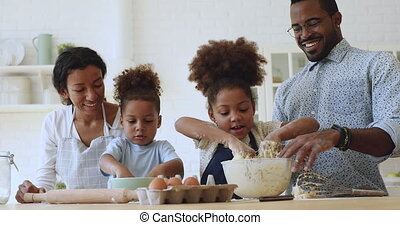 Cute small african kids kneading dough helping parents in kitchen