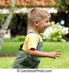 Cute small boy chasing soap bubbles