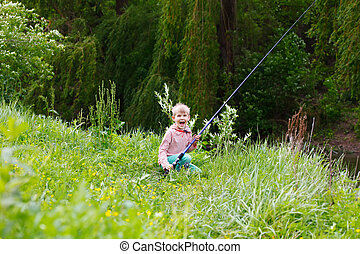 Cute small boy fishing on the river