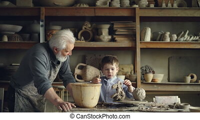 Cute small boy is playing with clay making ceramic toy in his grandfather's workshop. Grey-haired bearded man is looking at him with love and pride and talking.