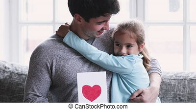 Cute small child girl congratulating smiling daddy with Father's Day.