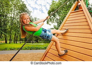 Cute small girl climbs on wooden construction