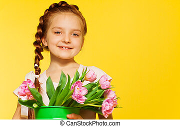 Cute small girl holding pail with pink tulips