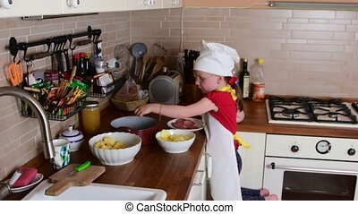 Cute small girl makes dinner. Small girl prepares food in the kitchen. Cute little girl dressed like a chef.