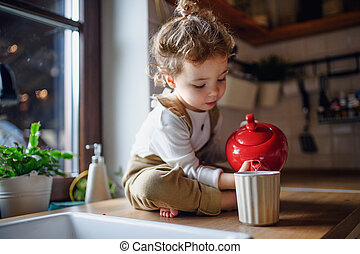 Cute small toddler girl sitting on kitchen counter indoors at home, pouring tea.