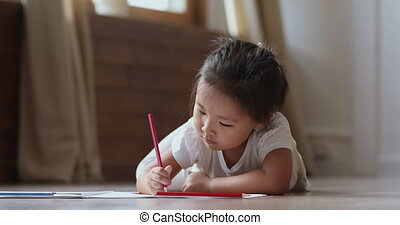 Cute small vietnamese kid girl drawing alone lying on floor...