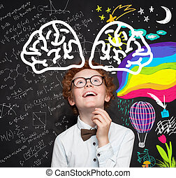 Cute smart child boy on blackboard background with maths formula and art pattern. Brainstorming, creativity and education concept