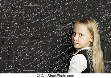 Cute smart child student on blackboard background with science formulas. Learning science concept.