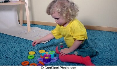 cute smart girl child set plastic toy fiddle pieces sitting on carpet floor