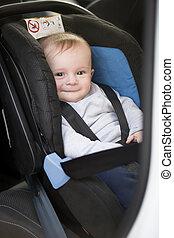 Cute smiling baby boy sitting in car child seat