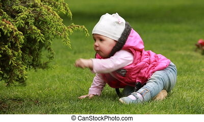 Cute smiling baby-girl crawling on a green grass in the city park.