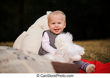 Cute smiling baby girl sitting on a blanket in the park