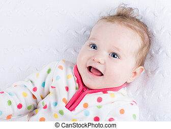 Cute smiling baby girl wearing a warm winter jacket playing on a