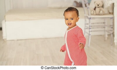 Cute smiling baby learning to walk
