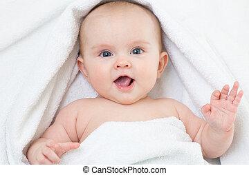 Cute smiling baby portrait lying on bathing towel
