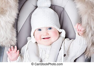 Cute smiling baby sitting in a stroller on a cold winter day