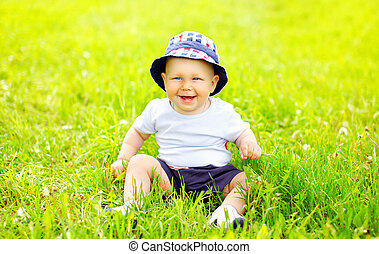 Cute smiling baby wearing a hat sitting on the grass in sunny summer day