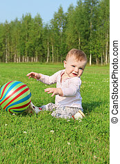 Cute smiling baby with ball sits on green grass on summer field