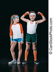 Cute smiling boy and girl in sportswear standing together isolated on black, activities for children concept