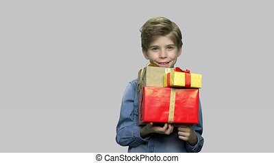 Cute smiling boy holding gift boxes.